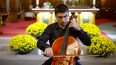 oltár : adult man is playing contrabass in catholic church in funeral day, solo of one classical instrument