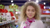 cicili bicili : young pretty girl is posing for camera in shop with decorations, she is playing with purple tinsel