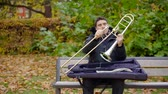 caz : Guy assembling a trombone sitting on bench in a park. Stok Video
