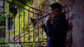 instrumentalist : Side view shot of a brunet jazz player playing a song on trombone outdoor in a park.