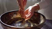 tibetano : woman is washing hands over old traditional indian bowl with patterns, water is pouring from up