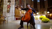 оркестр : adult man musician is playing violoncello in a church hall in front of altar, sitting on chair