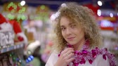 adornar : attractive young woman with curly blonde hair is looking at camera playfully in a store