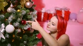 redhead : cheerful redhead woman is decorating new year tree in her apartment, putting ball on branch of spruce