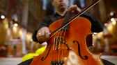 catholic : Close-up shot of a guy with cello in church, playing classical songs. Stock Footage