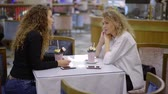 gossip : Two attractive blonde women with sweet milkshakes sitting and talking with each other in a empty cafe, cafe in the mall.
