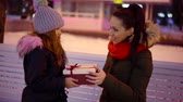 скромный : funny modest preschooler girl is presenting gift box for her mother outdoors in christmas evening