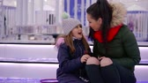 wintertime : cute little girl is sitting on a bench in winter park with her mother, they are chatting and kissing