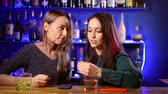juntar : celebration and lifestyle concept-happy women drinking strong alcohol and talking at the bar with mobile phones discussing gossip