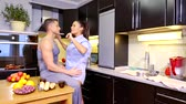 spouses : young husband and wife in the kitchen cute laugh and chat, drink tea Stock Footage