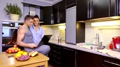 kolano : young successful couple of freelancers have lunch and work at home in the kitchen. a man holds a laptop on his knee Wideo