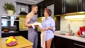 curlers : Sexy woman wearing mans shirt and in curlers talking with her man in home kitchen while cleaning fruits, casual day.