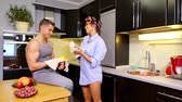 curlers : Beautiful young couple talking and smiling in kitchen. Stock Footage