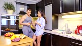 más : handsome young man and his beautiful brunette girlfriend are talking in kitchen in holidays Stock mozgókép