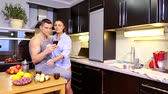 suíça : Young married couple having Breakfast in kitchen. watch funny news on your mobile device. there is a sandwich with cheese and sausage Stock Footage