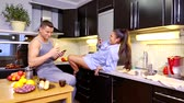 mobile kitchen : man and woman are having fun in kitchen, girl is photographing and filming her boyfriend