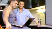nevetés : young happy couple sitting in kitchen watching laptop Beech and talking