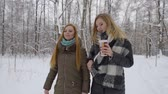 cachecol : two cheerful fashionable young girls walk in the winter forest. One drinks coffee and looks in the smartphone.