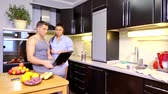 женат : pretty brunette woman is standing near with her husband looking on display of notebook in kitchen in home Стоковые видеозаписи