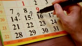 marcado : human is making notes and marks in calendar, writing question mark, encircling any dates Stock Footage