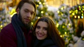 parceiros : portrait of a cute multiracial couple on the street in the winter evening amid the holiday lights. Jewish girl and her European man Stock Footage