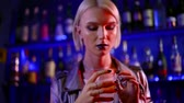 osobnost : portrait of a young homosexual blonde man in a night bar. to drink hard alcohol alone