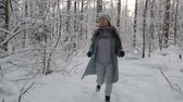 verfolgung : scared adult woman is fleeing in winter forest in daytime, looking back, she is tired, stopping Stock Footage