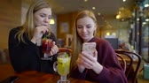 both : two women are drinking hot berry tea in cafe and watching pictures on display of mobile phone