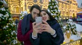 fotografieren : joyful man and woman are embracing outdoors and girl is taking selfies by smartphone Stock Footage