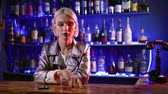homosexual : homosexual young man is looking like a woman is sitting in bar alone in evening, touching glass