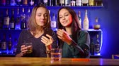 espíritos : two pretty young women are dancing near bar counter and viewing pictures in smartphone Stock Footage