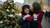 both : young bearded man is hugging and kissing his girlfriend, standing on square with christmas tree