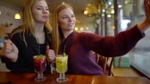 mulled : Two girls hanging out and taking selfies on smartphone.