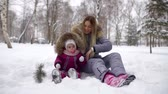 dia das mães : Mother playing with hed cute daughter sitting in a snowbank in a park, beautiful winter season.