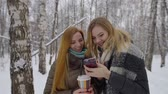 wintertime : Close-up portrait of a two young attractive blonde girls looking at smartphone excited and joyful.