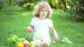 repolho : Happy child eating vegetables in spring park. Healthy eating concept Vídeos