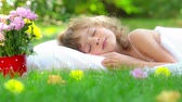 Happy child sleeping on green grass outdoors in spring garden Stock Footage