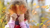 Happy child playing outdoors in autumn park. Slow motion
