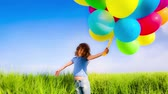 despreocupado : Happy child playing with multicolor balloons in spring field. Slow motion