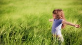 Happy child enjoying in spring field. Slow motion