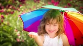 guarda chuva : Happy child walking in the rain. Funny kid with bright multicolor umbrella. Slow motion Vídeos