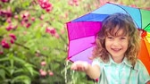 Happy child walking in the rain. Funny kid with bright multicolor umbrella. Slow motion Stock Footage