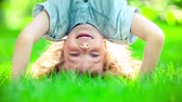 Happy child having fun in spring park. Funny kid standing upside down on green grass. Healthy lifestyle concept