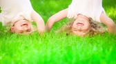 fitness : Happy children having fun in spring park. Funny kids standing upside down on green grass. Healthy lifestyle concept