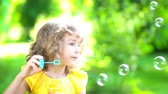 background : Happy child blowing soap bubbles in spring park. Kid having fun outdoors. Imagination and freedom concept. Slow motion from 120 fps