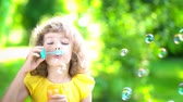 sabão : Happy child blowing soap bubbles in spring park. Kid having fun outdoors. Imagination and freedom concept. Slow motion from 120 fps