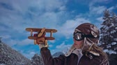 volando : Happy child playing with wooden airplane against winter sky background Archivo de Video