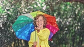 смеющийся : Happy child playing in the rain Стоковые видеозаписи