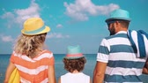 sen : Happy family on the beach. People having fun on summer vacation. Father, mother and child against blue sea and sky background. Holiday travel concept