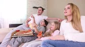 Young parents and their children are watching TV, eating pizza and smiling while sitting on couch at home